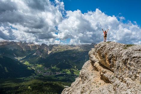 Eine Frau steht glücklich auf dem Gipfel eines Berges
