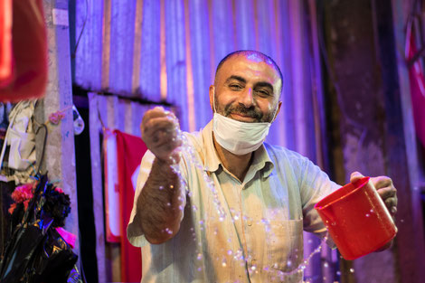 At the bazar in Izmir. A man watering his fish