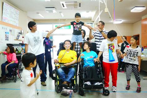 車いすの人、子ども、障害のない人が一体となって、組体操の扇を形作っている。