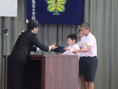 小学校の卒業式の壇上で、障害のある生徒が、同級生に導かれながら、堂々と卒業証書を受け取っている
