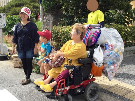 車いすの取っ手部分に、大袋いっぱいになった空き缶をぶら下げて街をゆく
