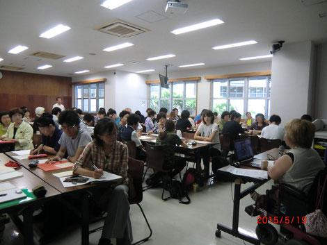 大学の講義室で、学生を相手に障害当事者が講師となり講義を行っている。