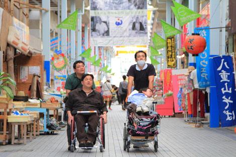 石垣島の商店街を介助者とともに歩く、新垣正樹さんと金城太亮さん