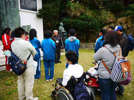 愛楽園の園内で、ハンセン病回復者の案内人の話を聞く中学生とイルカの障害当事者