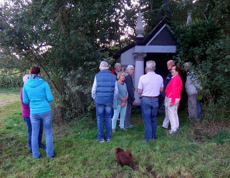 Foto: Lamke Eine Gruppe informiert sich beim Besitzer des Mausoleums, H.-P. Stelling über die historische Bedeutung des Mausoleums in Wingst-Weissenmoor.
