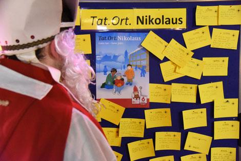 Bischof Nikolaus schaut sie die aufgeschriebenen guten Taten der Passanten in Dortmund an. © Theresa Meier