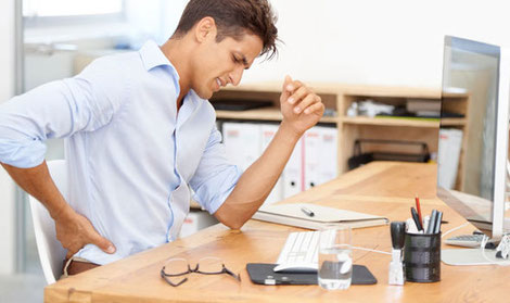 An Indian male executive seated on his desk suffering from back pain at his work desk