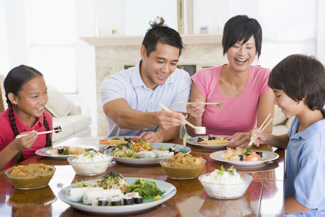 Asian family of four eating an asian meal with chopsticks
