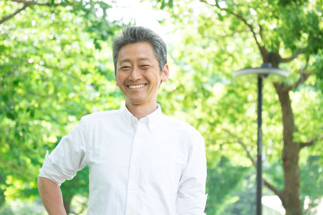 A calm and happy asian man in a white linen shirt at the park