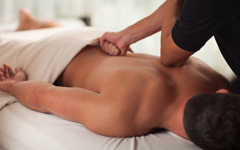 A man lying down on a massage bed while a rolfer works out the kinks in the body