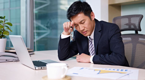 A male Singaporean executive sitting at his desk with his hand on his forehead frowning