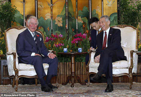 Prince Charles and PM Lee having afternoon tea in an room with oriental furnishings