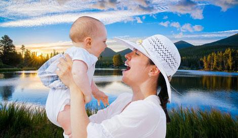 Strahlende Mutter die ihr kleines Baby hochhält und anlächelt.