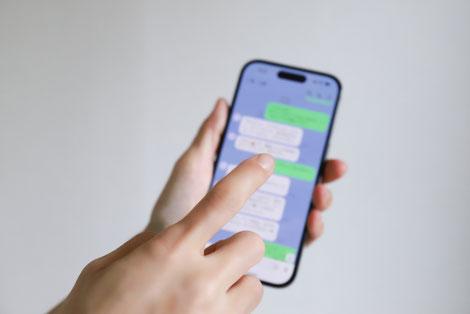 プライベート時間にスマートフォンを操作してSNSに投稿する女性社員。