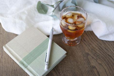 USBからデータを取り込み中のノートパソコン。傍らにコーヒーの入ったマグカップ、スマートフォン、黒のペン。