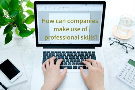 デスクの様子。ノートパソコンにコーヒーが入ったマグカップ。英字新聞のうえにスマートフォン、ボールペン、電卓が置かれている。