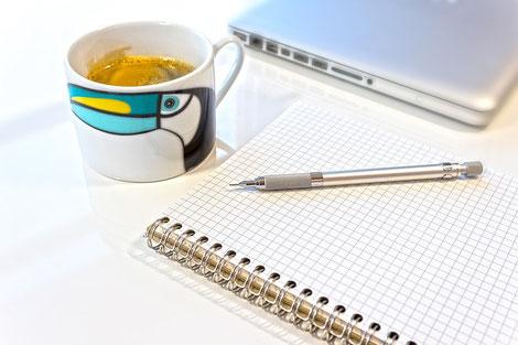 パソコンのキーボードの上にメモ帳とボールペンが置かれている。