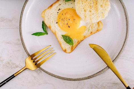 ピンク色の電卓、預金通帳、コーヒーの入ったマグカップがテーブルに並んでいる