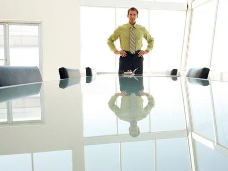 Geschäftsmann allein stehend am großen unbesetzten stark spiegelnden Konferenztisch im Büro