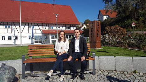 Der Leiter des Bad Saulgauer Ordnungsamtes, Herr Martin Brölz, testet mit seiner Mitarbeiterin das erste Mitfahrbänkle vor dem Dorfgemeinschaftshaus in Friedberg ein.