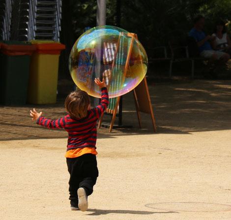 Kind in Bewegung - läuft einer großen Seifenblase nach