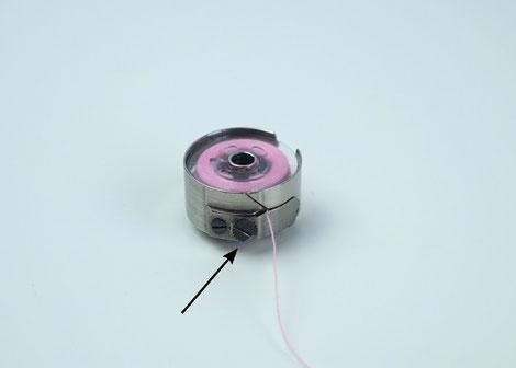 Die Spulenkapsel mit der Unterfadenspule, um die Unterfadenspannung einzustellen.