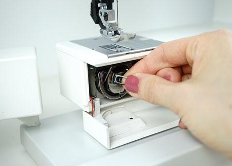 Die Greiferklappe öffnen und die Spulenkapsel herausziehen. Die Unterspule herausnehmen und die Nähmaschine ausschalten.