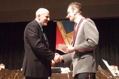 Musikpräsident Stephan Bucher (rechts) bedankt sich mit einem Präsent beim zurücktretenden Dirigenten Hanspeter Odermatt aus Alberswil.