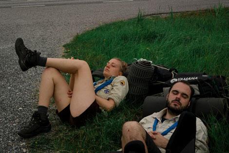 Pfadfinder mit blauen Halstüchern schlafen im Gras