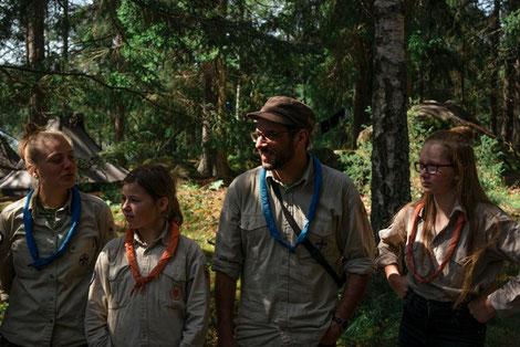 Pfadfinder im Wald mit orangen und blauen Halstüchern