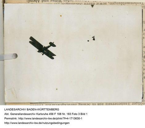 Foto eines gerade aus einem Flugzeug abgeworfenen, an einem Fallschirm befestigten Brieftaubenkorbs