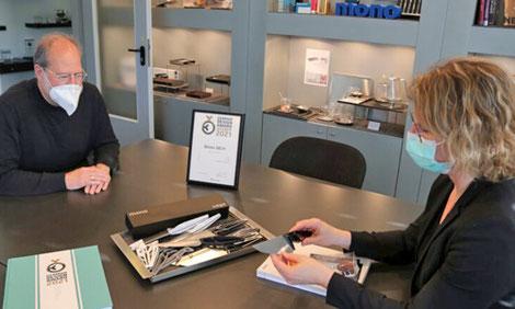 Firmenchef Wilhelm Seibel zeigt Bürgermeisterin Sandra Pietschmann das Messer SK59. Im Karton auf dem Tisch liegen erste Entwürfe des Messers, die mit einem 3D-Drucker hergestellt wurden. (Foto: Kreisstadt Mettmann)