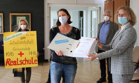 Dr. Regina Lenz überreicht Bürgermeisterin Sandra Pietschmann den Aktenordner mit den 3464 Unterschriften zum Bürgerbegehren Erhalt der Realschule. (Foto: Kreisstadt Mettmann)