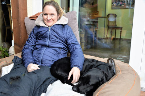 Frau im Rollstuhl mit Winterjacke Nina Hoffmann draußen auf der Terrasse mit schwarzer schlafender Labrador Hündin