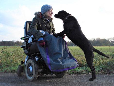 Frau Nina Hoffmann im Rollstuhl mit Mütze und Brille mit schwarzer Labrador Hündin auf der Wiese im Hintergrund Wald
