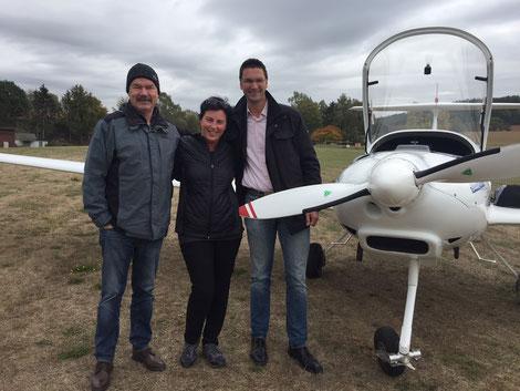 Die frisch gebackene TMG-Pilotin Sandra Luhn mit Prüfer Klaus Viehmann (r.) und Ausbildungsleiter Karsten Hofmann (l.)
