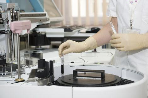 Großes Laborgerät (Zentrifuge) wird von einer Person im weißen Kittel bedient, Symbolabbildung