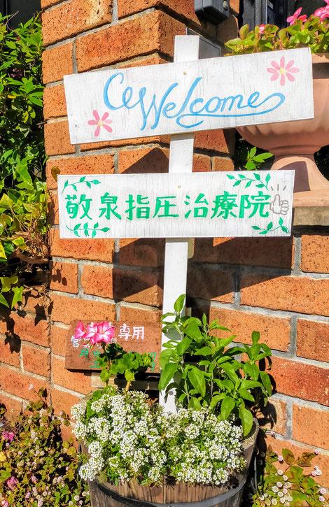 花に彩られた治療院の看板
