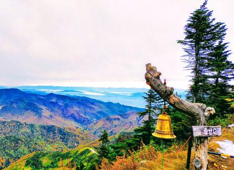 横手山山頂の幸せの鐘、近くの紅葉の山、山間に雲海、遠くにかすむ北アルプスの山並み