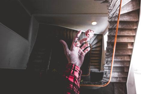 Bras et main d'homme avec manche de chemise rouge et rayures noires ayant jeté deux dès à jouer