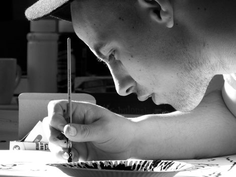 Photo en noir et blanc montrant un jeune homme avec une casquette en train de peindre et de prendre du plaisir
