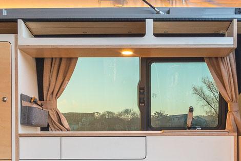 Ein offenes Hängeregal bietet zusätzlichen Stauraum im VanBUS