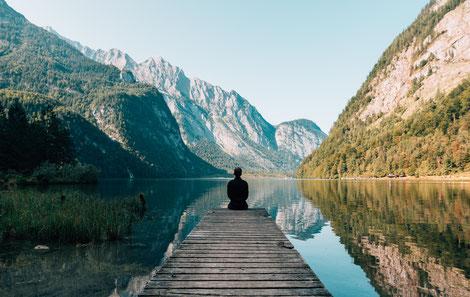 Person sitzt auf Steg, Blick in die Berge, Ruhe, Stille, Alleinsein