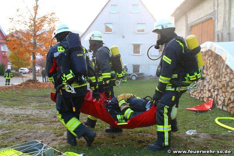 Sicherheitstrupp und Angriffstruppführer tragen den verletzten Truppmann aus dem Gebäude