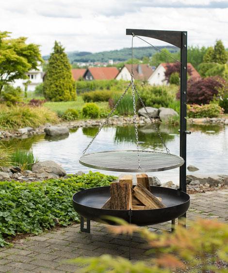 großer Schwenkgrill mit Feuerschale am Teich