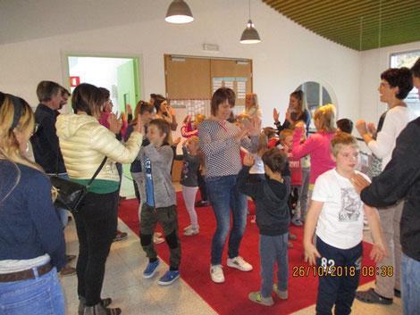 Eltern und Kinder begrüßen sich durch ein Klaschspiel