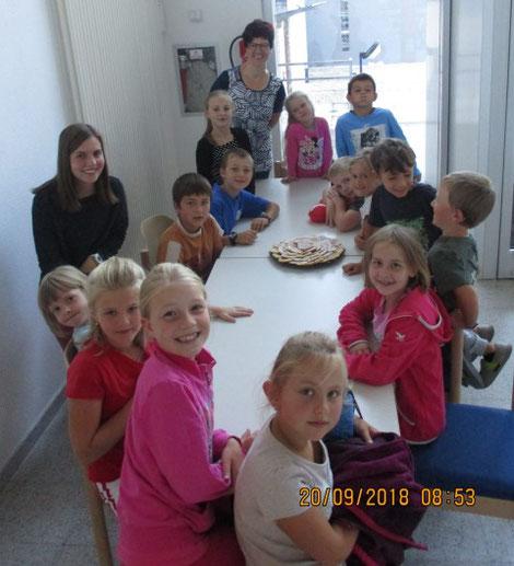 Kindergruppe sitzt am Tisch, sie freuen sich auf die Waffeln