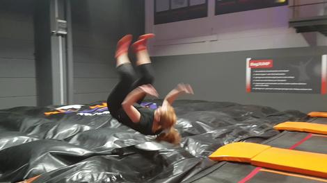 Frau macht Salto im Jump House vom Trampolin in ein Luftkissen.