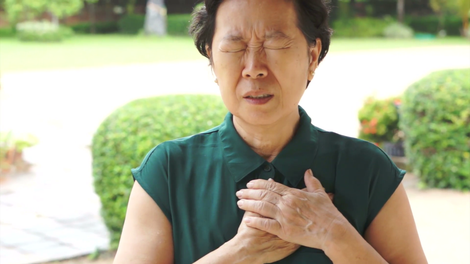 An asian senior woman frowning whilst she places both her hands to her heart in pain