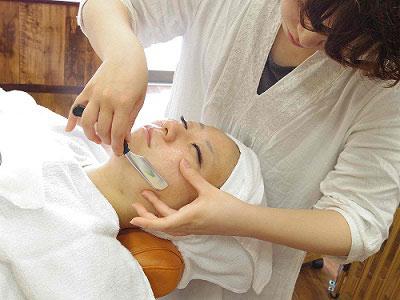 女性の理容師がお顔そりをしている写真
